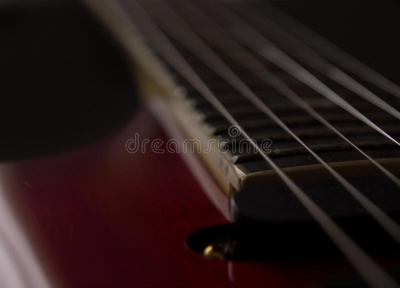 Detail of old electric guitar in low key light. Close-up, selective focus and black background stock image