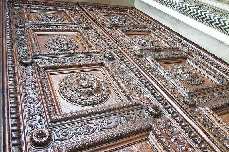 Detail of an old italian wooden carved door with floral decorati stock photos