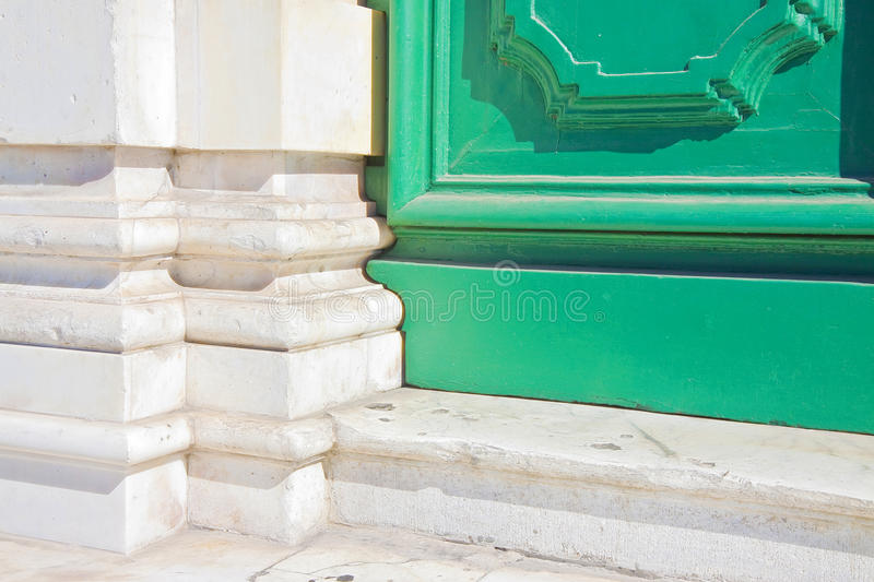 Detail of an old painted green wooden door against a white marble wall stock image
