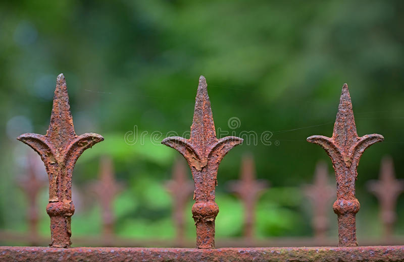 Detail of an old rusty fence with three fleur-de-lis stock image