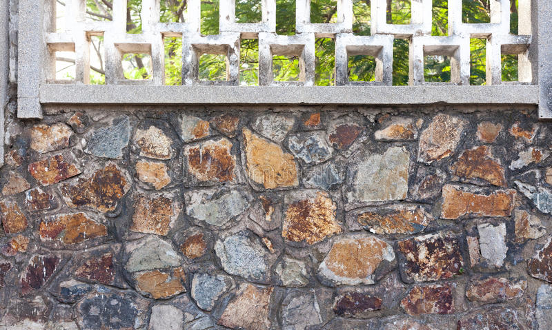 Detail of old stone wall with greenery in background. Texture background stock photo