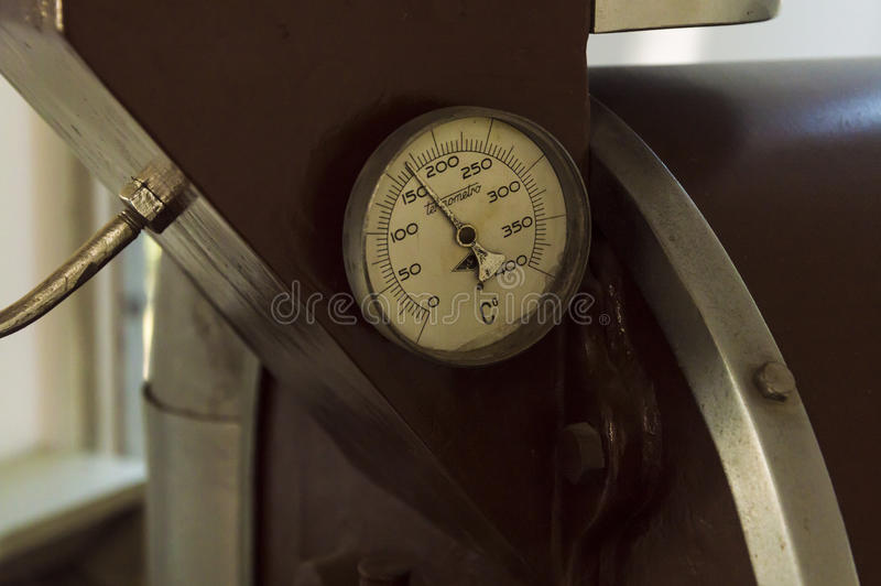 Detail of old thermometer, installed on abandoned coffee roaster, electric industrial machine royalty free stock images