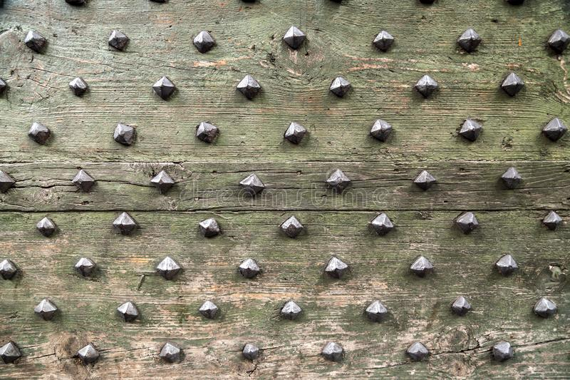 Detail from old wooden door with ancient metal rivets. Texture background, design element stock images