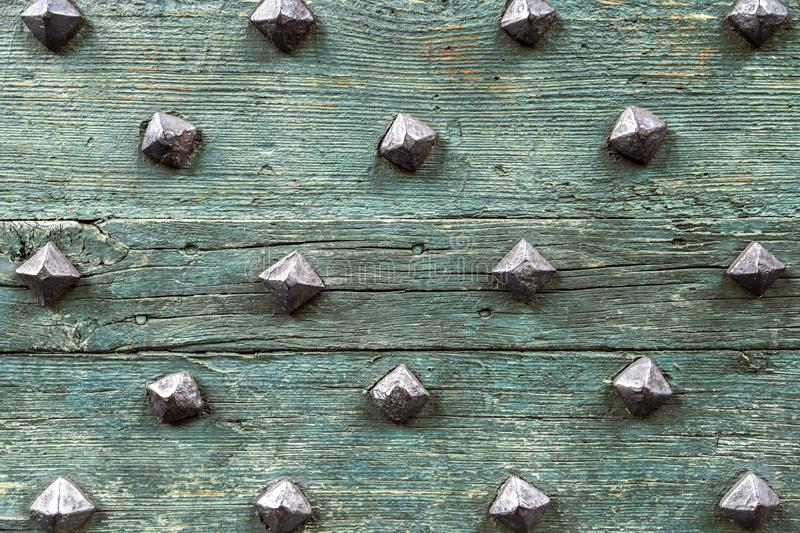 Detail from old wooden door with ancient metal rivets. Texture background, design element stock photo
