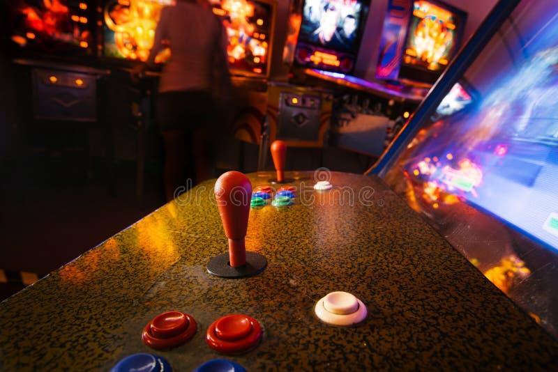 Detail op een bedieningshendel en knoopcontroles van een uitstekend arcadevideospelletje in een donkere ruimte stock afbeeldingen