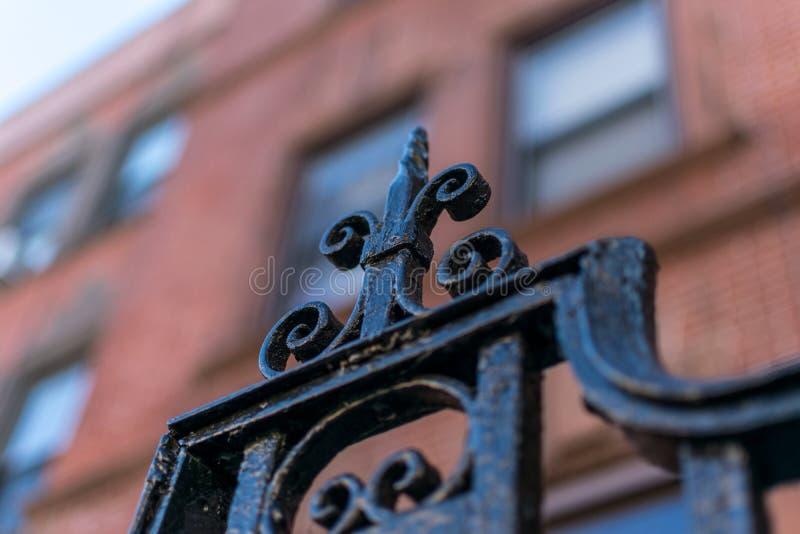 Detail op een smeedijzerpoort in de buurt van Harlem van de Stad van New York tegen een bokehachtergrond, Manhattan, NYC, de V.S. stock afbeelding