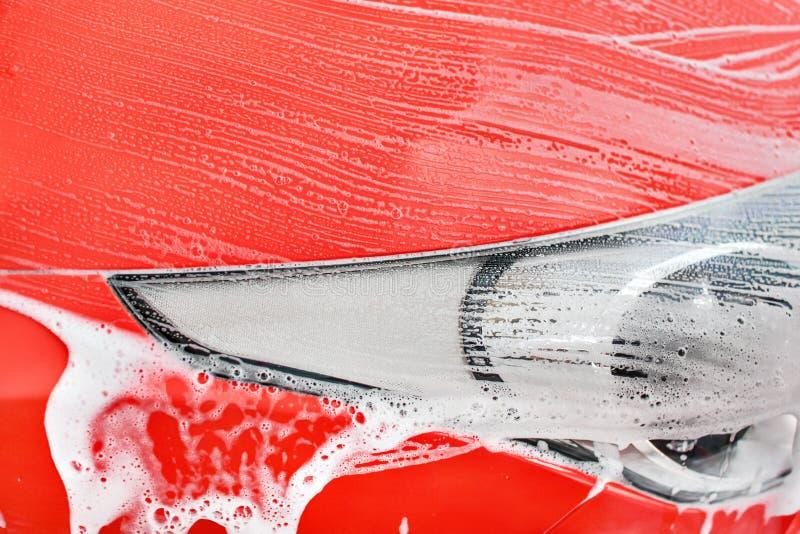 Detail op rood auto voordielicht in carwash wordt gewassen De kleur kan gemakkelijk met tint/verzadigingshulpmiddel worden verand stock foto