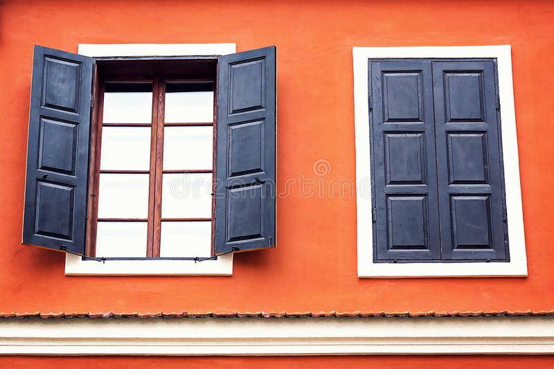 Detail of an open wooden iron vintage rustic windows on red cement old wall can be used for background. Brown black window shutter stock photo