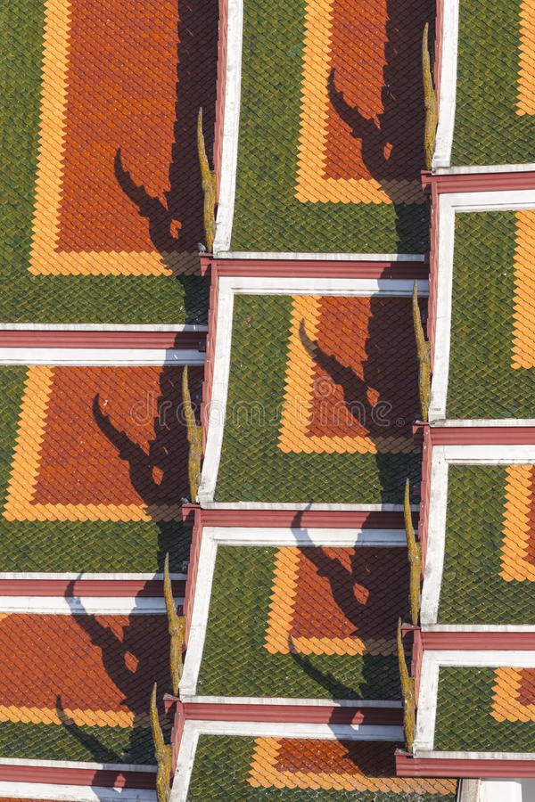 detail of the orange, yellow, and green roof tiles of Thai temple pattern royalty free stock image