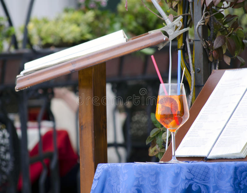 Detail outdoor terace in Venice. A glass cocktail on the table and menu book in outdoor terrace on wooden counter in Venice stock photography