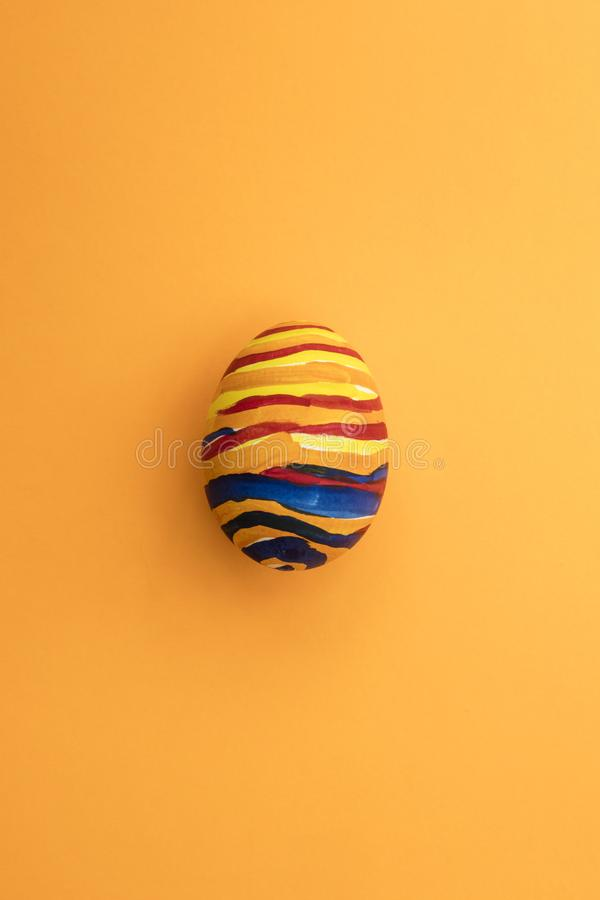 Detail of painted yellow Easter egg with red and blue stripes in orange background royalty free stock photo