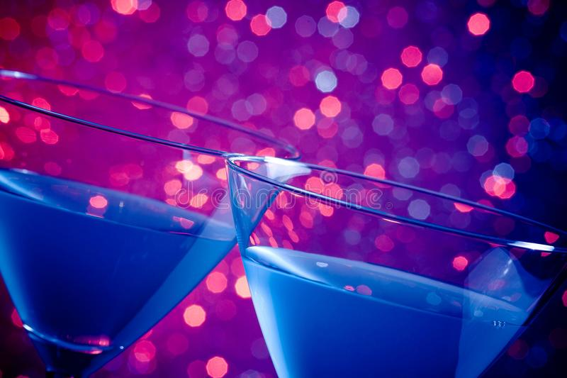 Detail of a pair of glasses of blue cocktail on table. Detail of a pair of glasses of blue cocktail on blue and violet tint light bokeh background royalty free stock photos