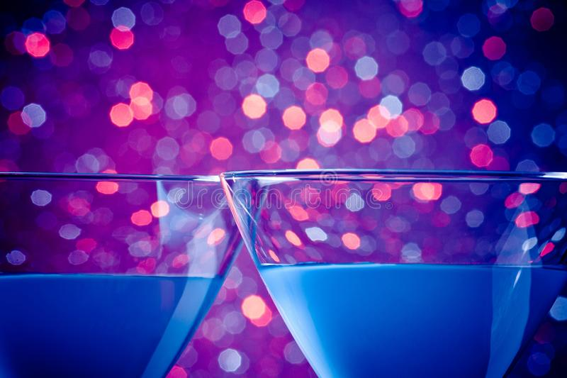 Detail of a pair of glasses of blue cocktail. On blue and violet tint light bokeh background with space for text stock image