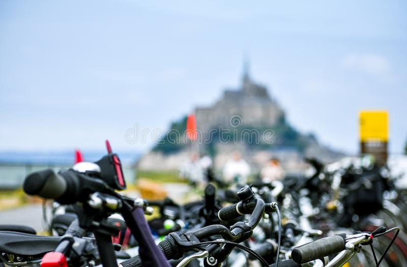 Detail of parked bicycles, with defocused silhouette of Mont Saint Michel, France.  stock photography