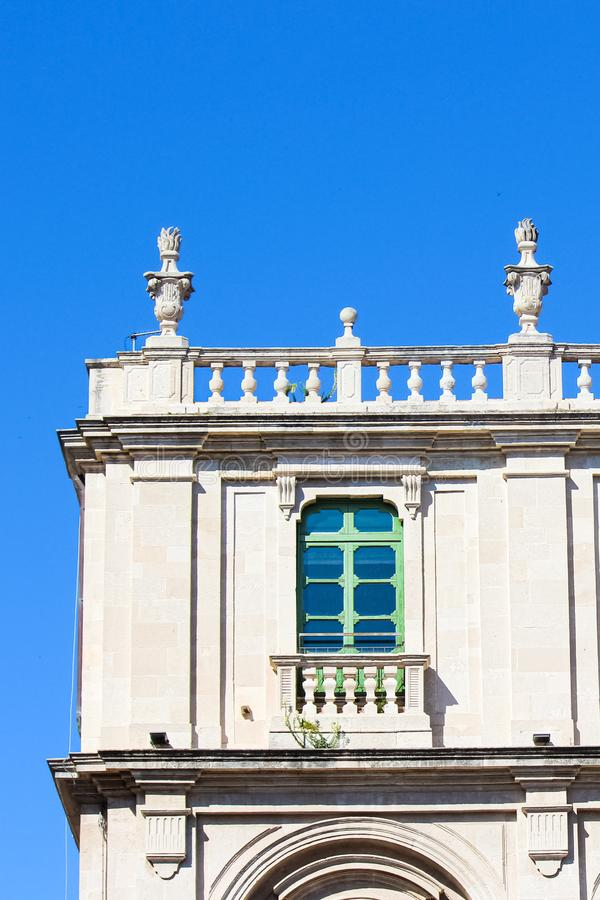 Detail photography capturing edge of historical university building in Catania, Sicily, Italy. Traditional bright facade. Green window and roof balcony stock images