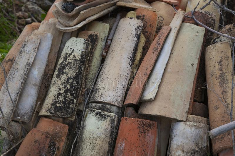 Detail of a pile of old tiles. Made of clay, very well placed and forgotten. Full of mold and fallen branches of a nearby tree royalty free stock images