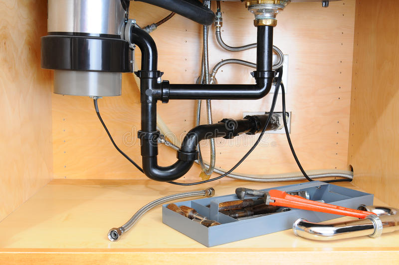 Under a Kitchen Sink. Detail of the plumbing system under a modern kitchen sink, with a plumbers tool tray and equipment. Horizontal format royalty free stock photography