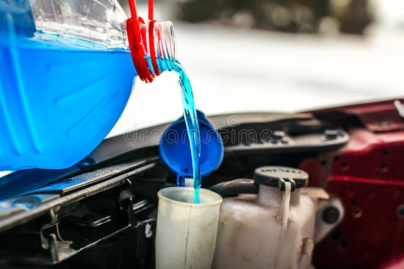 Detail on pouring antifreeze liquid screen wash into dirty car. From blue and red anti freeze water container royalty free stock images
