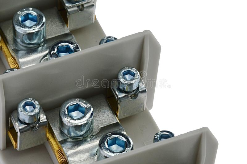 Detail of protective bonding conductor terminal with allen screws of various diameters and gray plastic frame, white background. Artificial interior light royalty free stock image