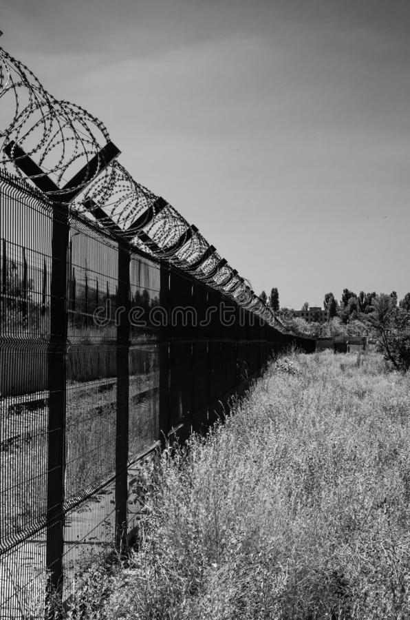 Metal fence with barbed wire protects the territory forbidden to visit and passage. Monochrome. Detail of the protective wall around the object royalty free stock image