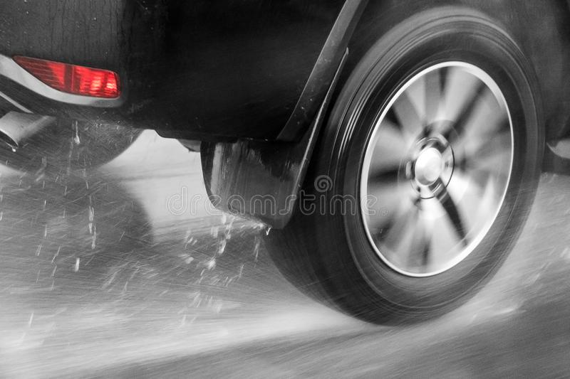 Detail of the rear wheel of a car driving in the rain stock images