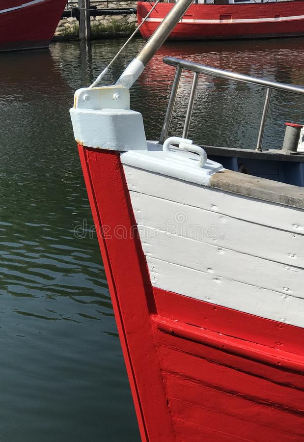 Red and white boat bow. Detail of red and white bow of a wooden boat at its mooring, showing carvel construction technique using planks stock photos