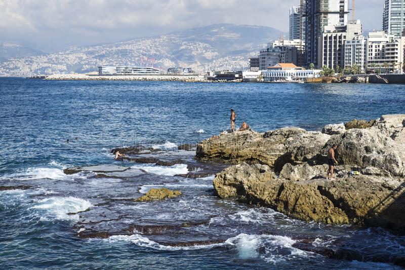 Detail of seacoast with natural pool and swimmers in Beirut with cityview on a sunny day, Lebanon stock photography