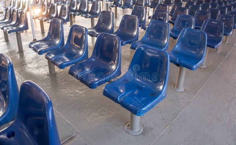 Auditorium. Blue empty plastic  chairs on line. Detail of seats in empty auditorium stock photo