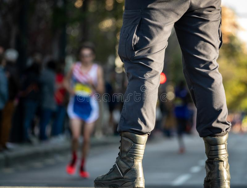 Security member guard and street with runners. Detail of security member legs and street with runners in the background royalty free stock images