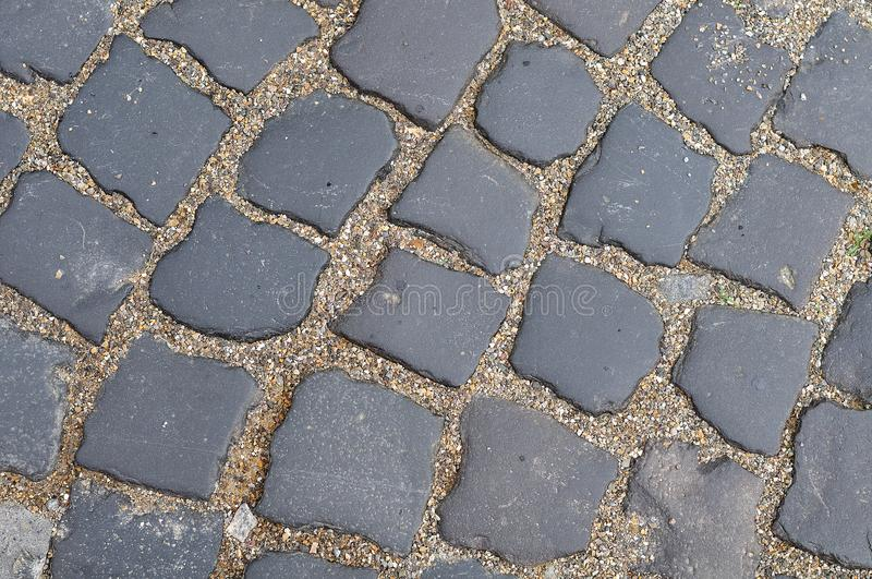 Detail of a sett stone pavement. Pavement of gray granite sett stones with fine gravel in interspace in street in old town royalty free stock image