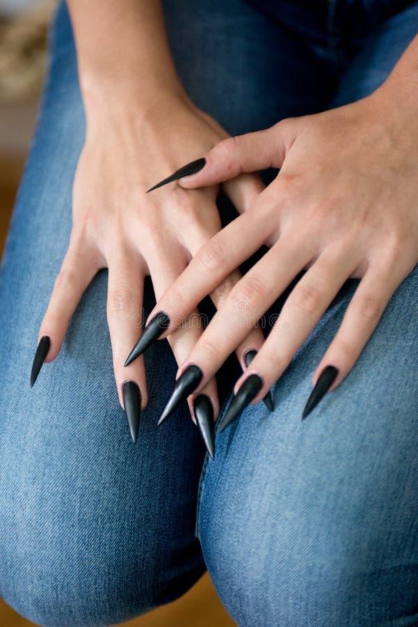 Detail shot of woman stiletto black nails. Detail shot of woman stiletto black and sharp nails stock photography