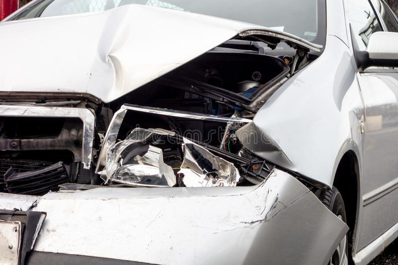 A detail of a silver modern car crashed in a frontal traffic accident stock image