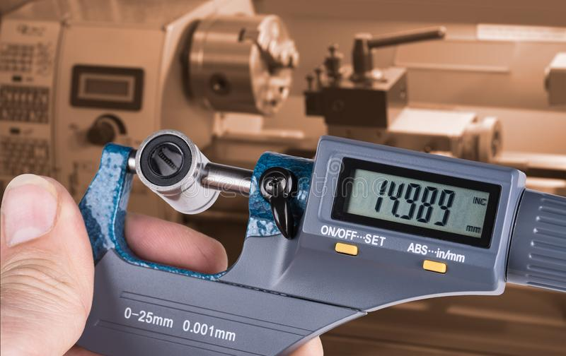 Detail of skilled worker`s hand with digital micrometer gauge. Accurate measurement of metal linear bearing by measuring tool and lathe in background stock photo