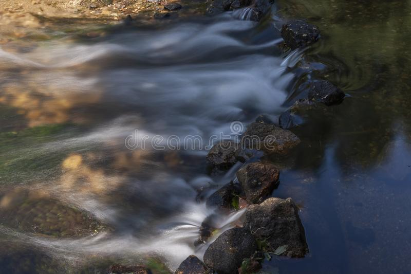 Detail of small dam built of stone. Crystalline water that flows through the stones of a small dam built by Man, forming small waterfalls royalty free stock image