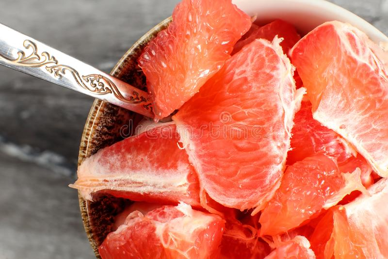Detail on small porcelain bowl with spoon, full of pink grapefruit cut into pieces. royalty free stock photography