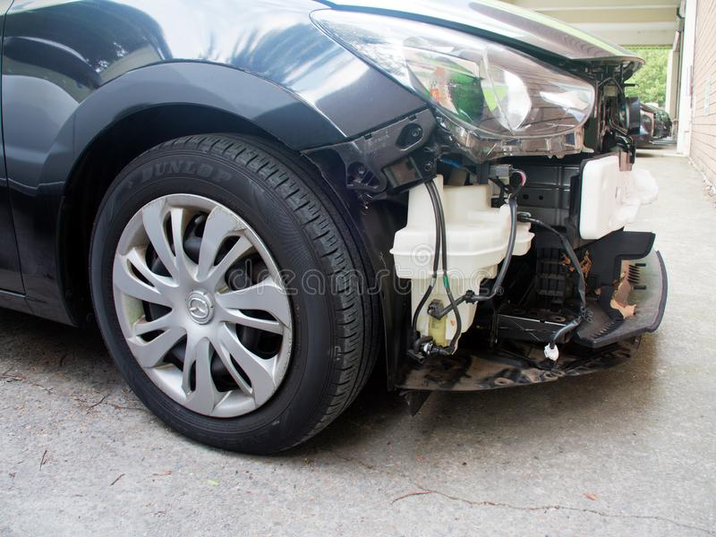 Detail of Smashed Car Front End Damage. Detail of a small black car with extensive front end damage from front rear collision. Demonstrates contemporary crumple stock photography