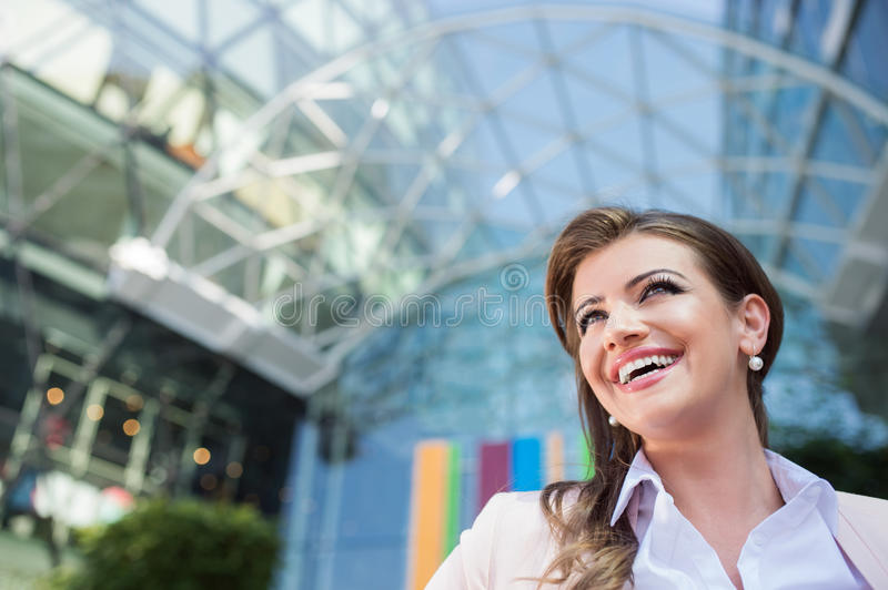 Detail of smiling businesswoman against glassy modern office building royalty free stock images