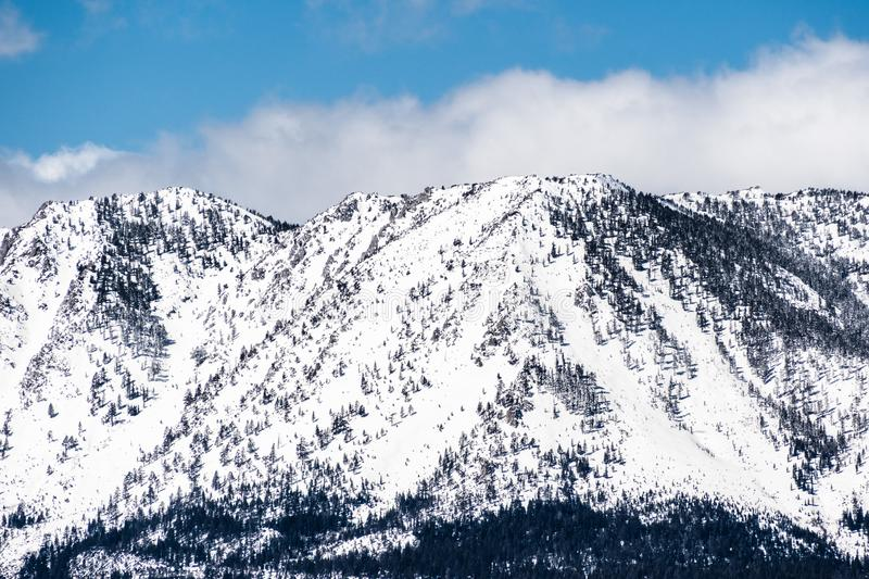 Detail of the snow covered Sierra mountains as seen from the shoreline of south Lake Tahoe, California royalty free stock image