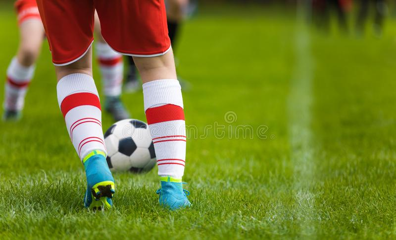 Detail Soccer Background. Close up legs and feet of football player in white socks and blue cleats playing game on green grass. Pitch. Footballers in red jersey stock photo