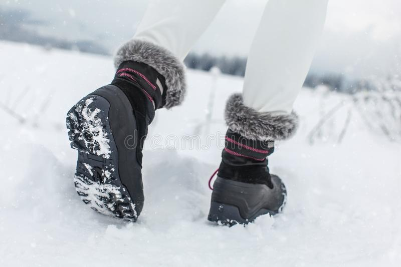 Detail on sole of black winter shoes with purple details. Worn by girl walking in snowy country in winter royalty free stock photography
