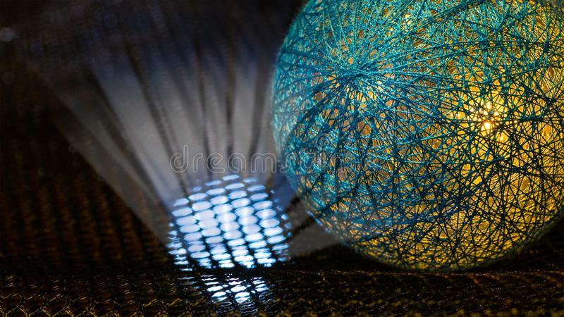 Detail of a sphere covered by net from fibers and mystery light rays in black space. Abstract background. Idea of danger, nuclear weapons, radiation, technology stock photo