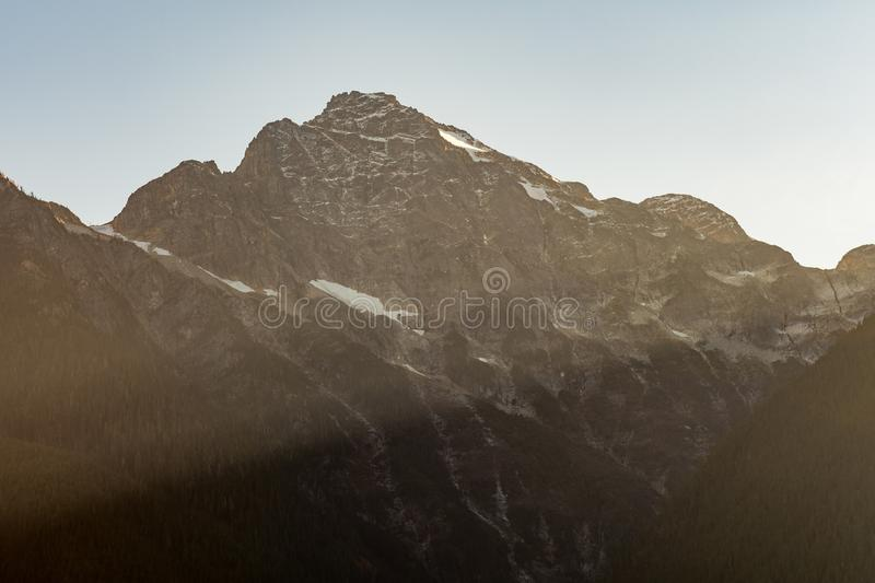 Detail of the sun`s rays passing between the snowy mountains next to Diablo Lake, in North Cascades royalty free stock image
