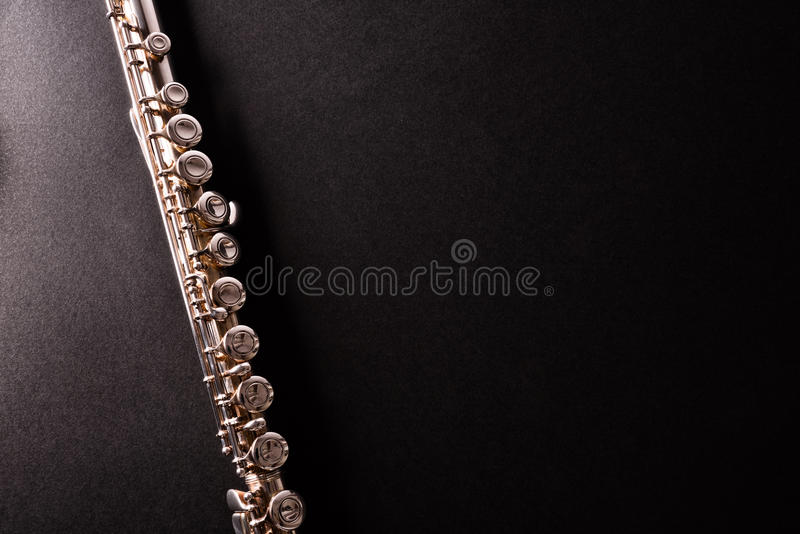 Detail of tansverse flute on black table top view royalty free stock image