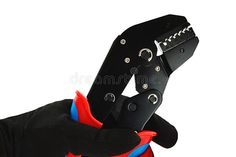 Detail of terminal crimping press pliers with closed jaws, held in left hand in thin black nylon/polyester/spandex glove. White background stock images