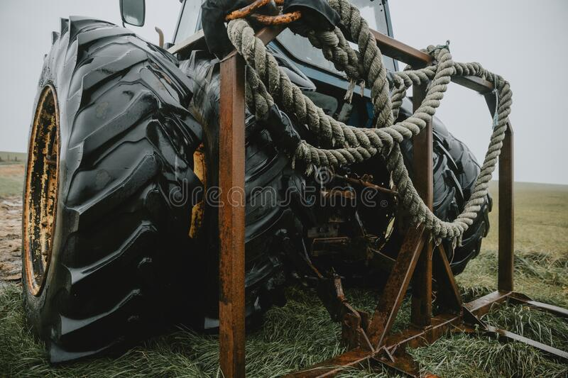 Detail of the thick wet rope coiled and hanging on the rear rusty frame on the back part of an old abandoned Tractor with huge dou stock photo