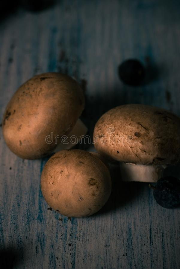 Detail of three Brown edible mushrooms spilled on vintage wooden board royalty free stock image