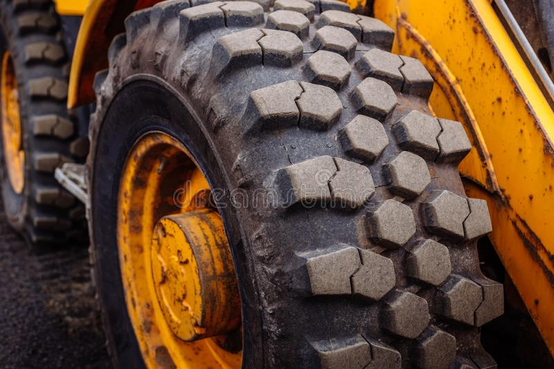 Detail on tire track pattern on a yellow heavy duty digger excavator royalty free stock image