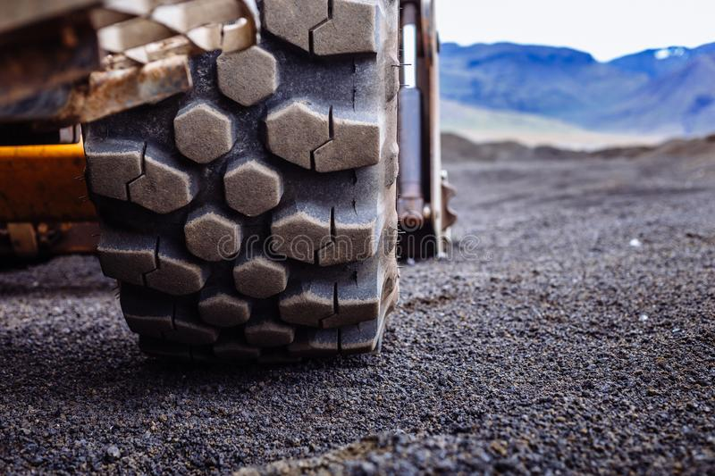 Detail on tire track pattern on a yellow heavy duty digger excavator stock image