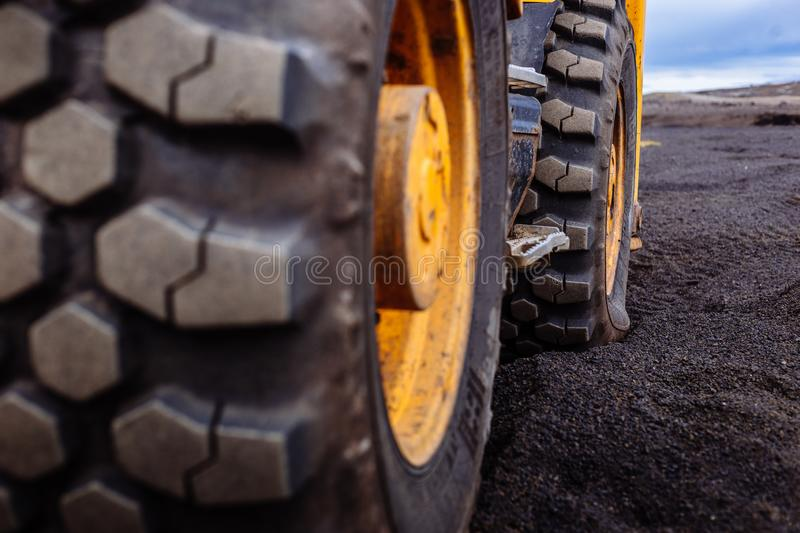 Detail on tire track pattern on a yellow heavy duty digger excavator royalty free stock photo