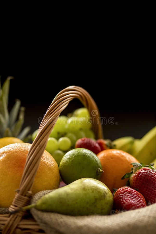 Detail from top on a basket full of fresh bio fruit on a dark backgrou royalty free stock images
